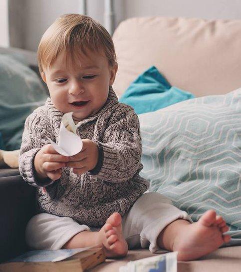 Söt glad baby pojke hemma leker med citronplatta