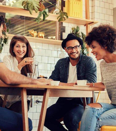 Glada unga vänner som har kul på ett kafé