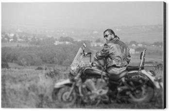 Impressão em Alumínio (Dibond) Biker brutal com desgastar barba jaqueta de couro e óculos de sol sentado em sua motocicleta em um dia ensolarado, que prende o capacete. horizontal da imagem. Visão traseira. Tilt turno efeito de borrão da lente. Preto e branco