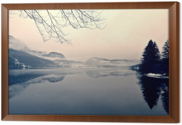Ingelijst Canvas Snowy winter landschap op het meer in zwart-wit. Zwart-wit beeld gefilterd in retro, vintage stijl met soft focus, rode filter en wat lawaai; nostalgische concept van de winter. Lake Bohinj, Slovenië.