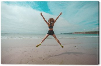 Leinwandbild Junge Frau macht Stern springt am Strand
