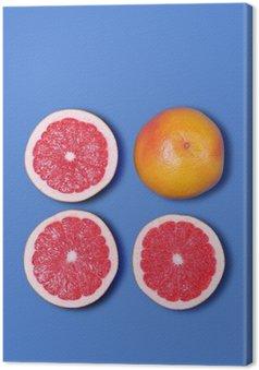 Leinwandbild Minimal-Design. Frische Grapefruit auf einem blauen Hintergrund