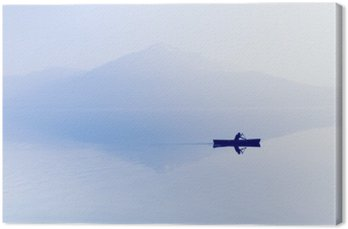 Leinwandbild Nebel über dem See. Silhouette der Berge im Hintergrund. Der Mann schwimmt in einem Boot mit einem Paddel.