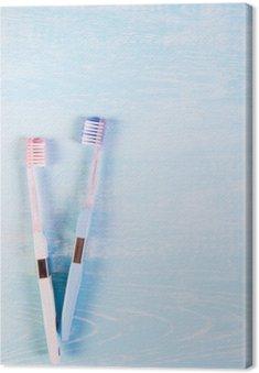 Leinwandbild Zwei Zahnbürsten und Kamillenblüten auf einem hellen Hintergrund. Das Konzept der Naturkosmetik für die Gesundheit. Du mich. Blick von oben