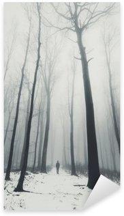 Naklejka Człowiek w lesie z wysokich drzew w zimie