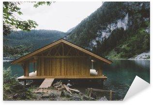 Naklejka Dom drewniany na jezioro z gór i drzew