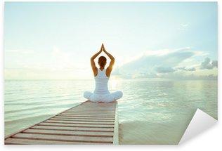 Naklejka Kaukaski kobieta uprawiania jogi na brzegu morza