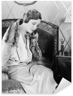 Naklejka Pixerstick Młoda kobieta siedzi na łóżku w sypialni, mówiąc na telefon