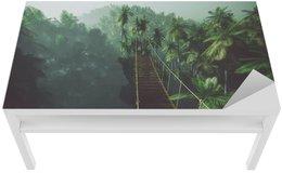 Naklejka na Biurko i Stół Rope bridge in misty jungle with palms. Backlit.