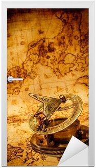 Naklejka na Drzwi Archiwalne Kompas leży na starożytnej mapie świata.