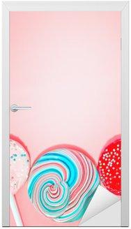 Naklejka na Drzwi Różowe tło z kolorowymi Cukierki