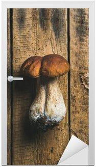 Naklejka na Drzwi Świeże surowe białe lesie grzyby i suchy liść na brudny drewnianych tle, widok z góry, pionowa kompozycja