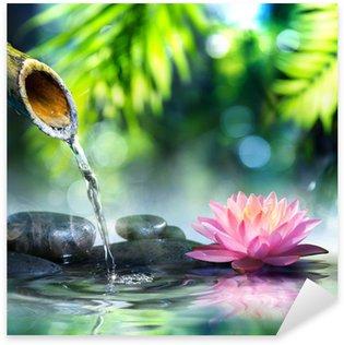 Naklejka Pixerstick Ogród zen z czarnych kamieni i różowym lilii wodnej