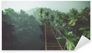 Naklejka Rope bridge in misty jungle with palms. Backlit.
