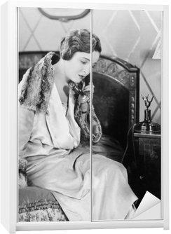 Nálepka na Skříň Mladá žena sedí na posteli v ložnici, mluví po telefonu