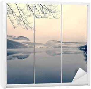 Nálepka na Skříň Zasněžené zimní krajiny na jezeře v černé a bílé. Monochromatický obraz filtrován retro, vintage stylu s měkkým zaměřením, červeným filtrem a některé hluku; nostalgické pojetí zimy. Jezero Bohinj, Slovinsko.