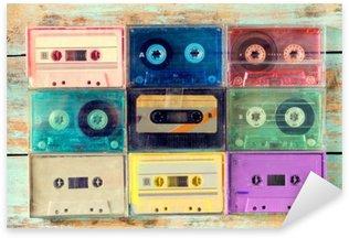 Nálepka Pohled shora (viz výše) záběr retro kazety s páskou na dřevěném stole - vintage barevné styly efekt.
