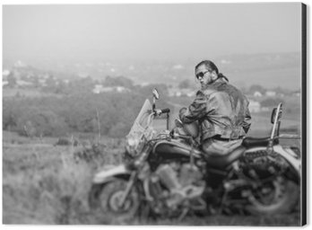 Obraz na Aluminium (Dibond) Brutal rowerzysta z brodą na sobie skórzaną kurtkę i okulary siedzi na motocyklu w słoneczny dzień, trzymając hełm. Pozioma obrazu. Widok z tyłu. Przesunięcie obiektywu efekt rozmycia Plandeka. Czarny i biały