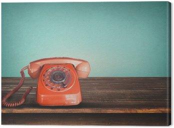 Obraz na Plátně Retro červený telefon na stůl s vintage zelené pastelové pozadí