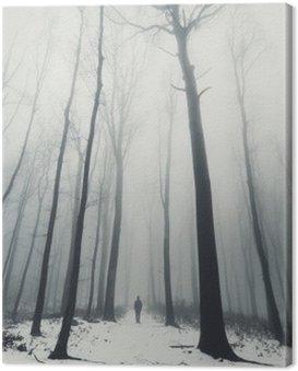Obraz na Płótnie Człowiek w lesie z wysokich drzew w zimie