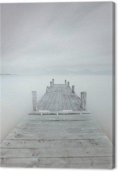 Drewniane molo na jeziorze w nastroju pochmurny i mglisty.