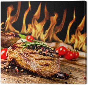 Obraz na Płótnie Grillowane steki wołowe z płomieni na tle
