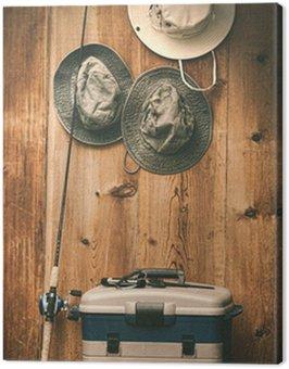 Obraz na Płótnie Kapelusze wiszące na ścianie z sprzętem rybackim