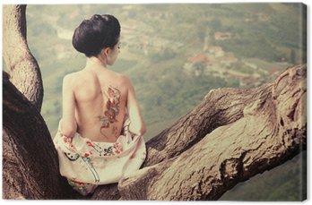 Obraz na Płótnie Kobieta z wężem tattoo siedzi na gałęzi drzewa