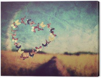 Obraz na Płótnie Kształt serce z motyli na tle zabytkowe pola