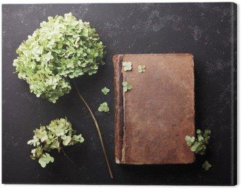 Martwa natura z starej książki i suszonych kwiatów hortensji na czarnym rocznika tabeli widoku z góry. Płaski lay stylizacji.