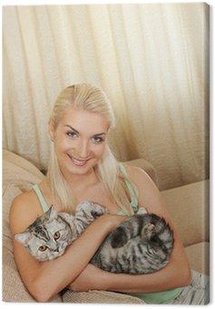 Obraz na Płótnie Młoda kobieta z kotów stitting na kanapie