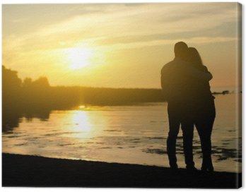 Obraz na Płótnie Młoda para korzystających zachód słońca. Dwie sylwetki.