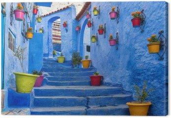 Obraz na Płótnie Niebieski schody i ściany ozdobione kolorowymi doniczek, Chefchaouen medina w Maroku.