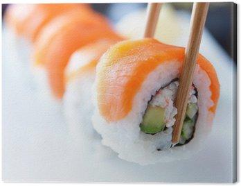 Obraz na Płótnie Podnosząc kawałek sushi z pałeczkami