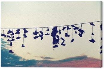 Obraz na Płótnie Retro stylizowane sylwetki buty wiszące na kablu o zachodzie słońca, nastoletnie koncepcji buntu.