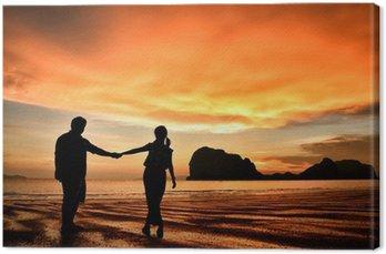 Obraz na Płótnie Romantyczna para trzymając się za ręce na plaży o zachodzie słońca