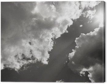 Obraz na Płótnie Słońce przebija się przez chmury. Czarno-białe zdjęcie