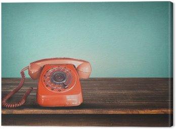 Stare retro czerwony telefon na stole z rocznika zielonym tle pastelowych