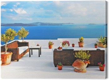 Stoliki na zewnątrz i kanapy na tarasie na dachu z widokiem na morze w Oia