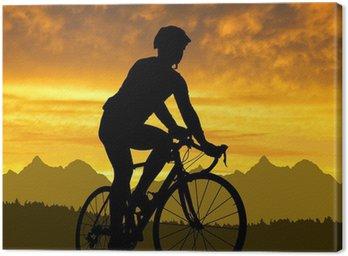 Obraz na Płótnie Sylwetka rowerzysty na rowerze na drogach na zachodzie słońca