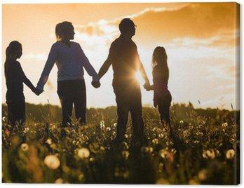 Obraz na Płótnie Szczęśliwa rodzina na łące o zachodzie słońca