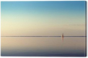 Obraz na Płótnie Woda krajobraz z białego łodzi żaglowej na spokojnych wodach w świetle zachodzącego słońca. Stonowanych i przetwarzania zdjęć.