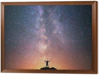 Obraz w Ramie Człowiek i Wszechświat. Osoba stoi na szczycie wzgórza obok Drogi Mlecznej z rękami podniesione do powietrza.