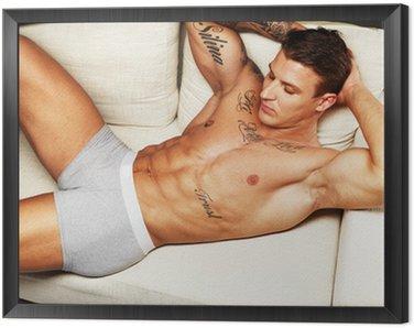 Obraz w Ramie Człowiek z pięknym mięśni tułowia w bielizna leżącego na kanapie