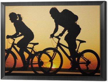 Obraz w Ramie Młoda para na rowerach na zachodzie słońca