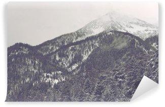 Omyvatelná Fototapeta Mraky se pohybuje přes vzdálený vrchol hory