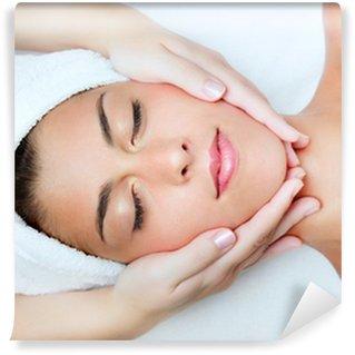 Papier Peint Vinyle Belle jeune femme recevant un massage du visage.