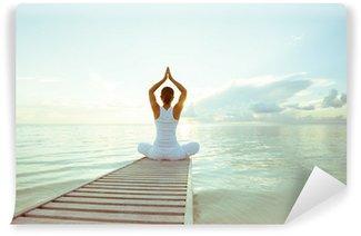 Papier Peint Vinyle Caucasien femme pratiquant le yoga au bord de la mer