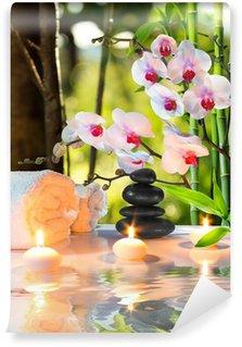 Papier Peint Vinyle Composition de massage spa avec des bougies, des orchidées, des pierres dans le jardin