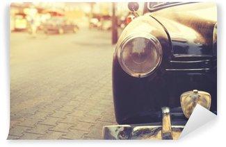 Papier Peint Vinyle Détail de la lampe de phare voiture classique garée en milieu urbain - style d'effet de filtre cru